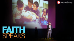 Mother standing on a stage, in front of a projector screen that displays a picture of her five young children.