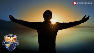 Man facing the sunrise with arms out stretched