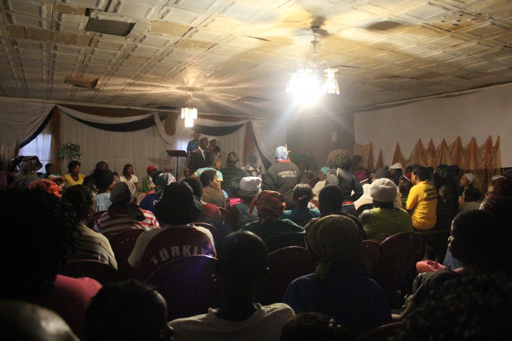 minister preaching in a filled hall to south africans
