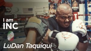 Man in a boxing ring with gloves with an intense look on his face with text overlay I am INC, LuDan Taquiqui.