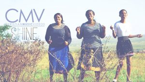 "Three African women with traditional face painting singing in field with text overlay: ""Shine"""