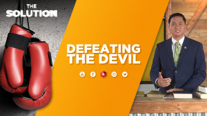 A man standing at a table with books and boxing gloves hanging on the wall with text overlay Defeating the Devil.