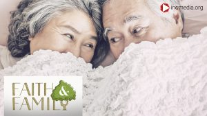 elderly couple looking at each other under blanket