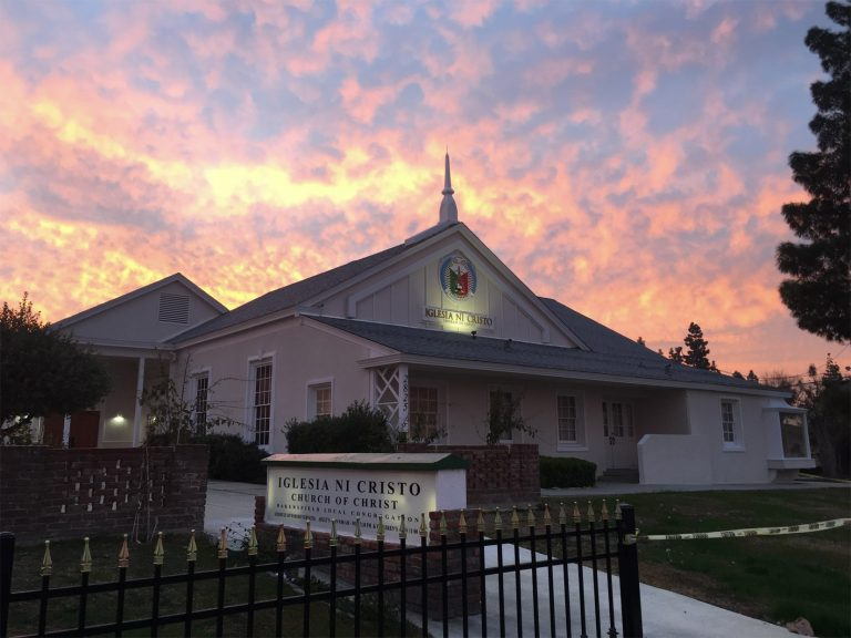 Front exterior of the Bakersfield house of worship with the sunset behind it.