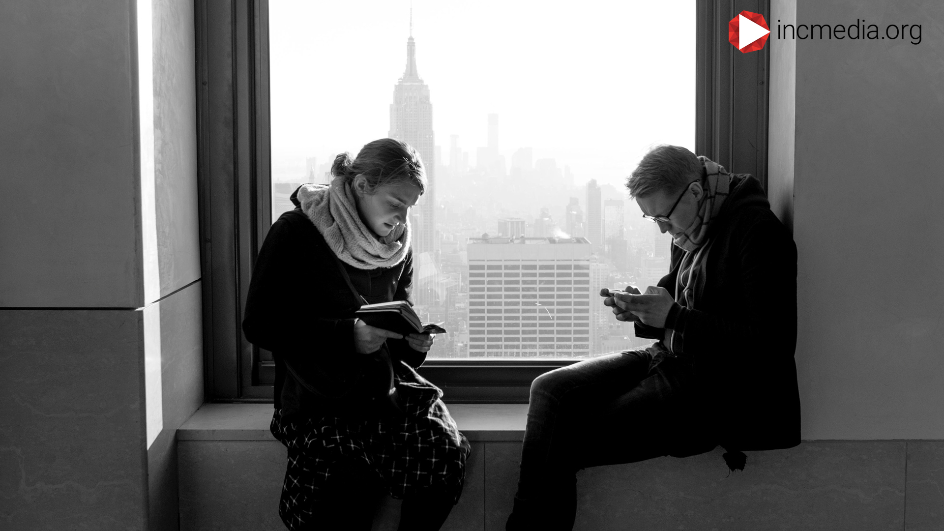 Two people at the window staring at their phones