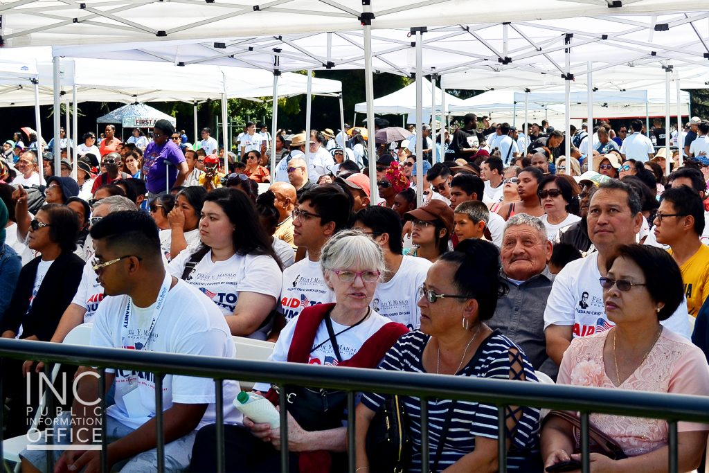Hundreds of Oakland residents sitting in the shade enjoying the Aid to Humanity event.