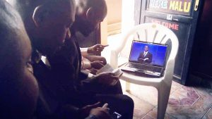 Three men watching a video on a laptop of a Church Of Christ Minister preaching