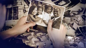 A pair of hands holds a single photo of a smiling family; on the table beneath is a pile of photos spread out.