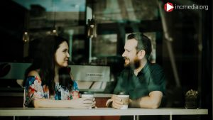 Man and wife looking at each talking over coffee.